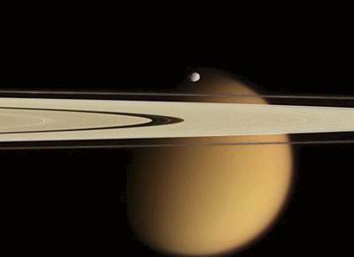 Saturn's rings and the moon Epimetheus in front of the cloud-covered moon Titan